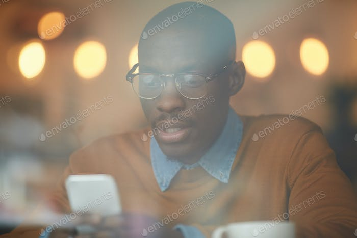 African-American Man Using Smartphone in Pub