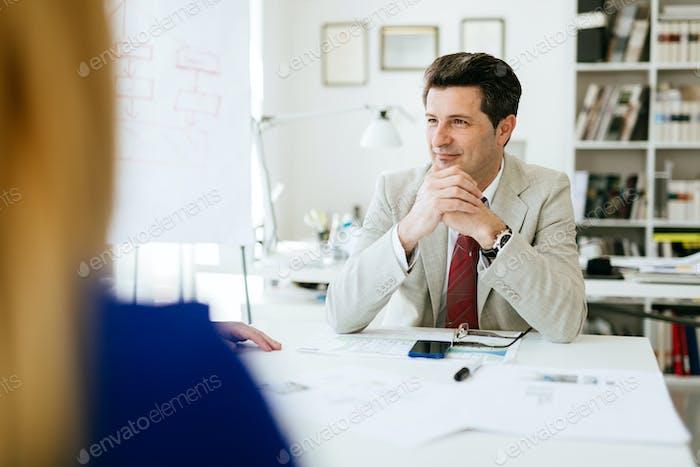 Директор компании сидит за столом