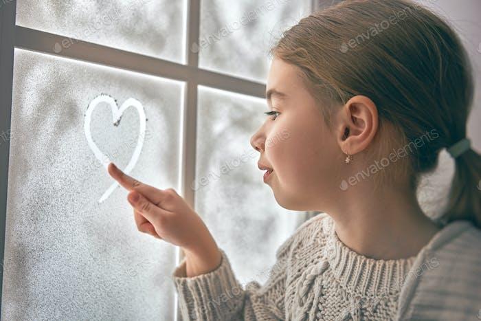 Mädchen sitzt am Fenster