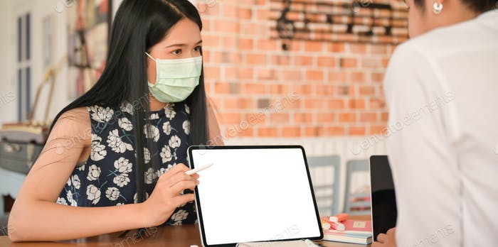 Female insurance agent wearing a mask is introducing a coronavirus health package with a tablet.