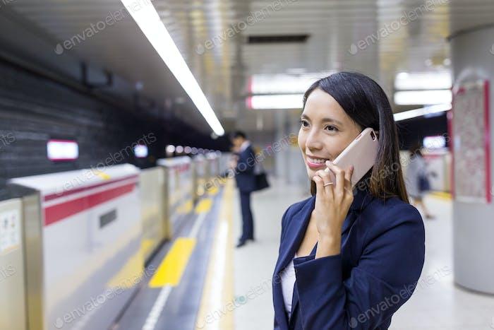 Бизнесвумен разговаривает с мобильным телефоном на вокзале