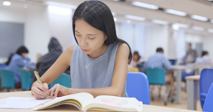 Student working on her homework at library