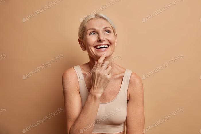 Portrait of cheerful middle aged European woman smiles broadly concentrated above has perfect well c