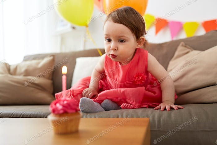girl blowing to candle on birthday cupcake at home