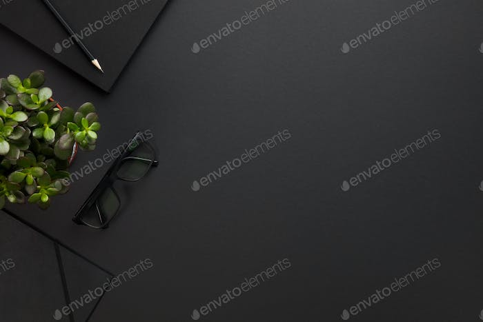 Thumbnail for Top view of black office desk with notebook and supplies