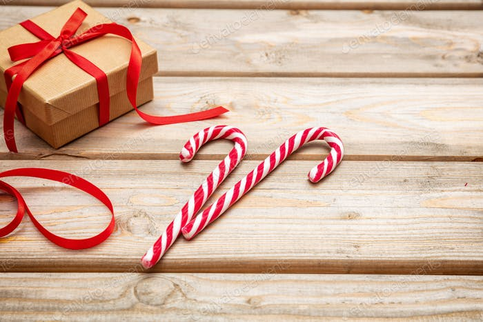 Candy canes and a gift box with red ribbon on wooden background, copy space