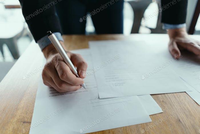 Успешный бизнес-человек подписывает документы в современном офисе
