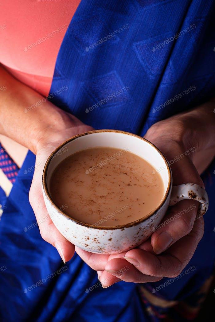 Frau hält eine Tasse Masala Tee