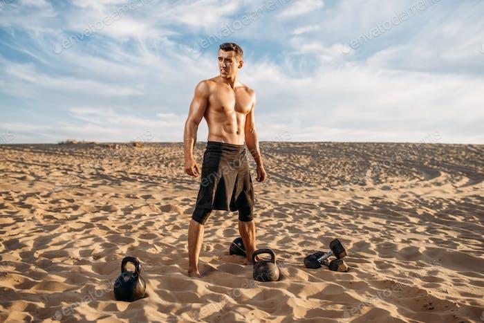 Athlete doing exercise with dumbbells in desert