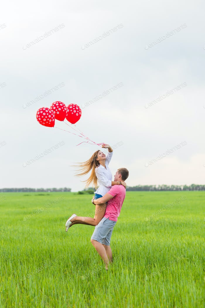 Man and woman on the field with red balloons. Happy couple on nature