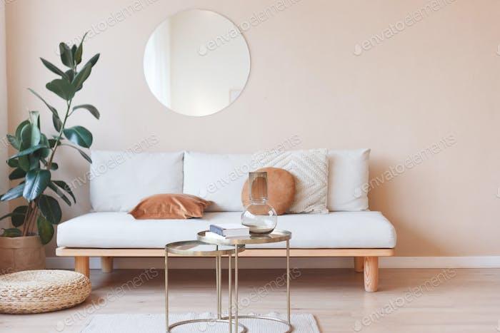 Wohnzimmer mit Sofa, Spiegel und Ficus