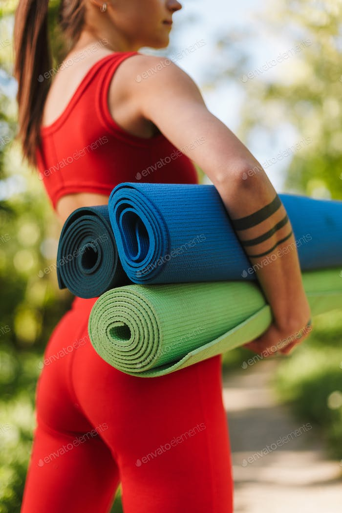 Young woman body in red jumpsuit standing from back with yoga mats in hands in park