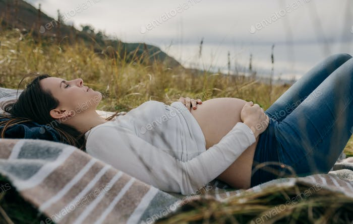 Pregnant woman caressing her tummy sleeping