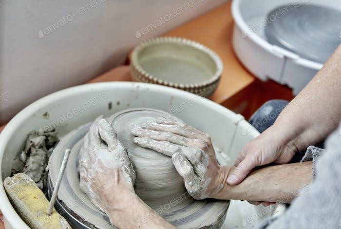 Una persona sentada en el plato giratorio de la rueda de un alfarero, con las manos sobre un bulto de arcilla húmeda, siendo enseñada a manejar