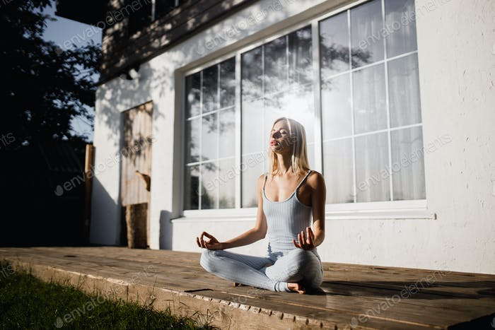 Young woman is practising yoga sitting in the lotus position on a wooden podium in the garden with