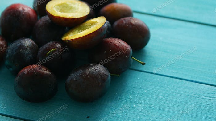 Purple plums on blue wood