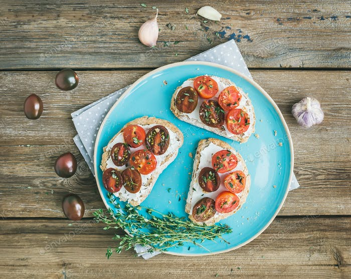 Rustic breakfast set of sandwiches with soft cream-cheese, cherr