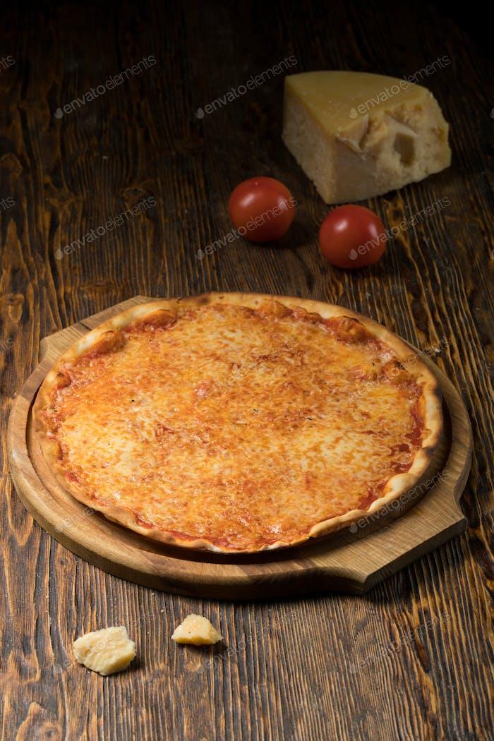 Pizza, Tomaten, Käse, Olivenöl auf einem Holztisch
