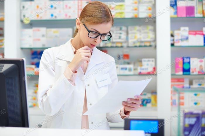 Female pharmacist checking documents at drugstore