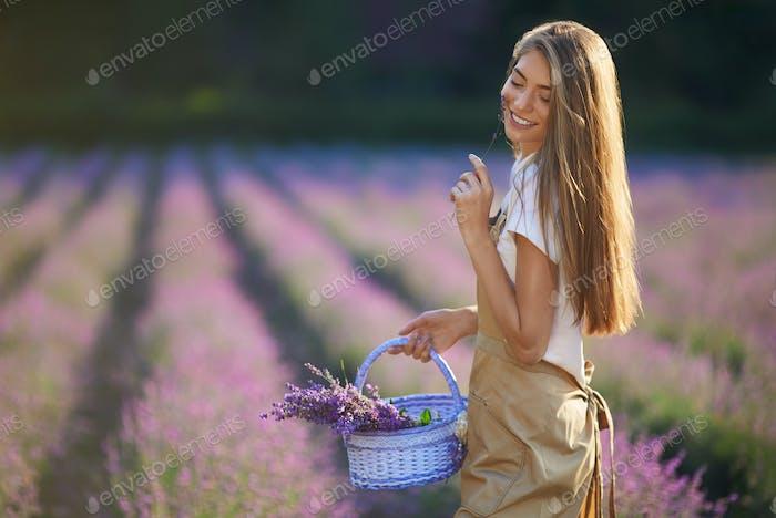 Chica feliz caminando con cesta, parches de lavanda