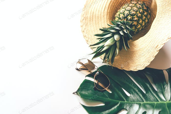 Summer concept with straw hat, sunglasses, monstera leaf and pineapple.