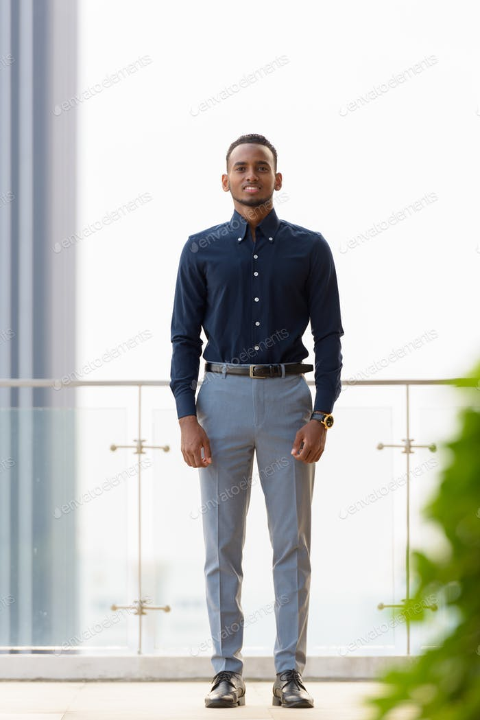Full length shot of happy African businessman outdoors at rooftop