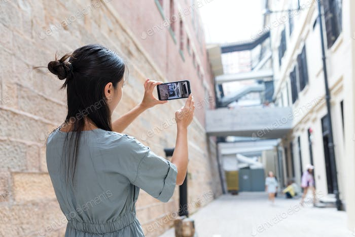 Woman taking photo of the street