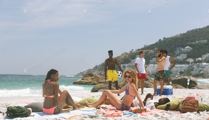 front view of multi ethnic group of friends relaxing and enjoying at beach on a sunny day