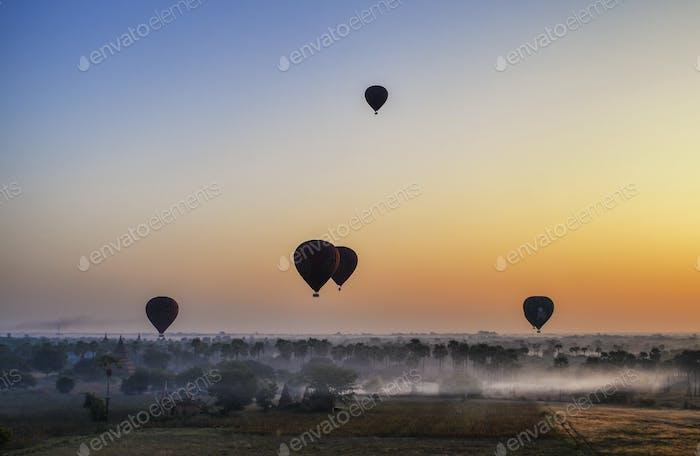 Heißluftballons über Landschaft mit entfernten Tempeln bei Sonnenuntergang, Bagan, Myanmar.