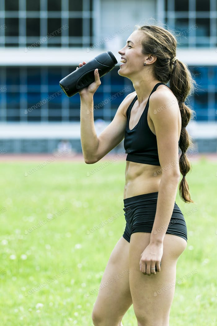 Girl athlete drinking water