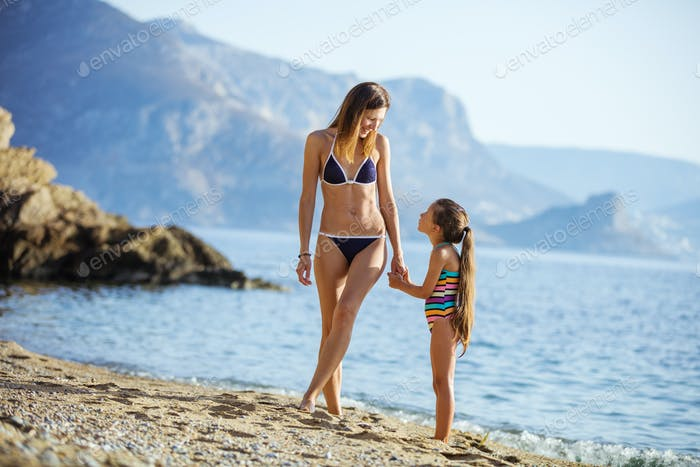 Young woman and her daughter on beach