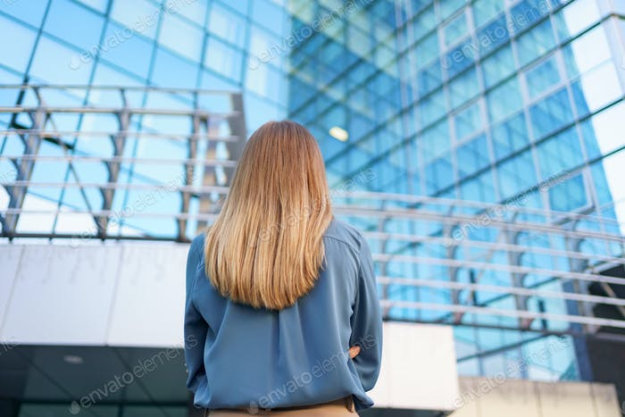 Back view woman looking business building