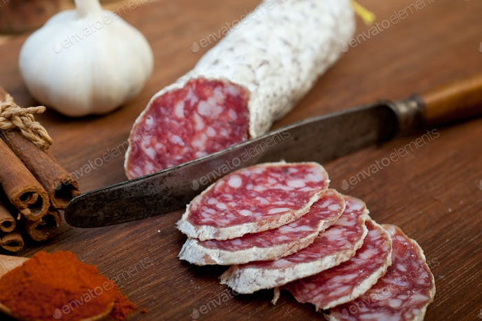 traditional Italian salame cured sausage sliced on a wood board
