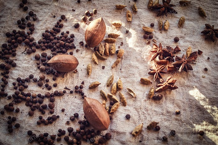 Close-up photo. Black peppercorn, beans, cinnamon, pecan on linen fabric.