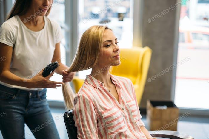 Glückliche junge Frau und Friseur mit Fan machen heißes Styling