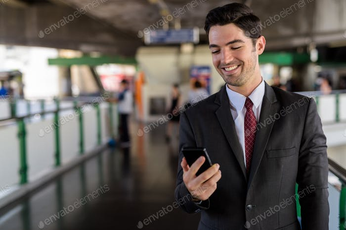 Portrait of happy businessman in city using mobile phone