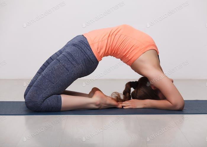 Beautiful sporty fit yogi girl practices yoga asana Kapotasana