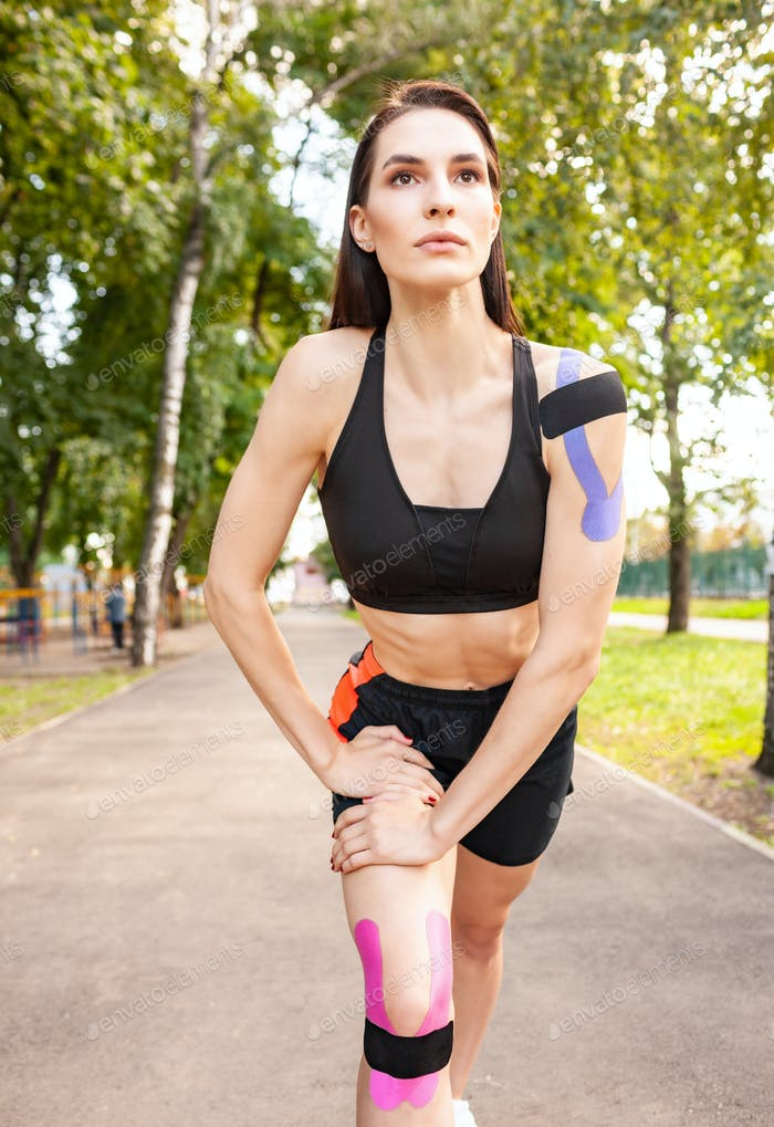 Young woman with kinesiotaping warming up outdoors