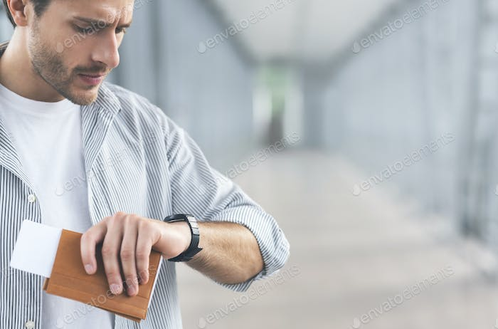 Worried man looking at watch, waiting for boarding at airport