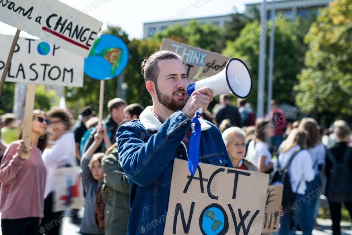 Man with placards and amplifier on global strike for climate change, shouting.