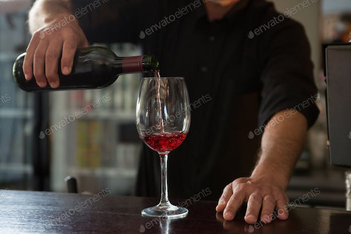 Waiter pouring wine in the glass