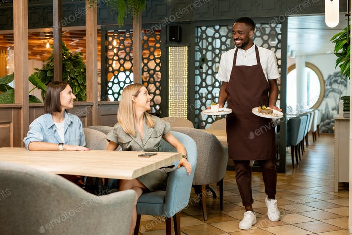 Smiling young waiter of African ethnicity carrying desserts for relaxed females