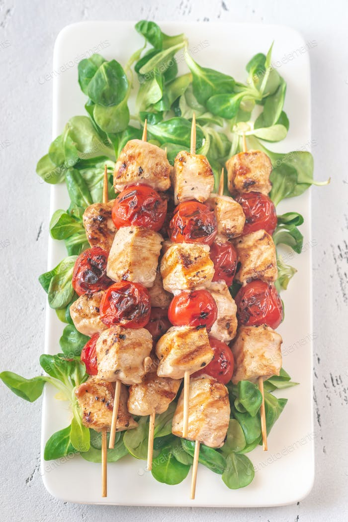 Grilled chicken skewers on the white plate