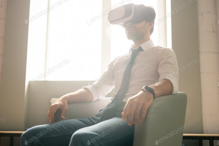 Serious calm young businessman immersed into virtual reality