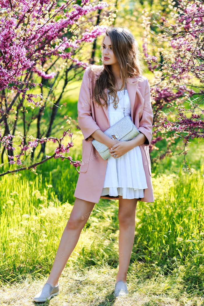 Attractive pretty young woman in walking in garden of spring time.