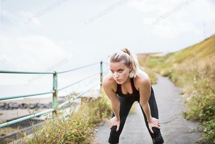 Young sporty woman runner in black activewear standing outside by the seaside, resting.