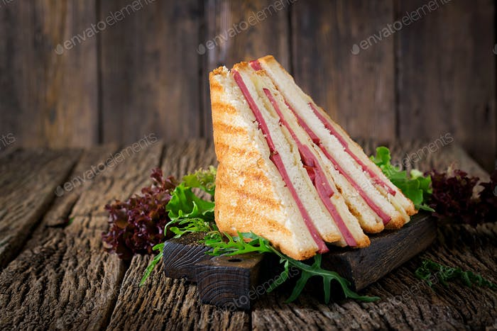 Club sandwich - panini with ham and cheese on wooden background. Picnic food.