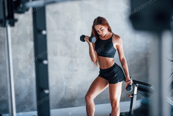 Young fitness woman is in the gym with dumbbells in hands