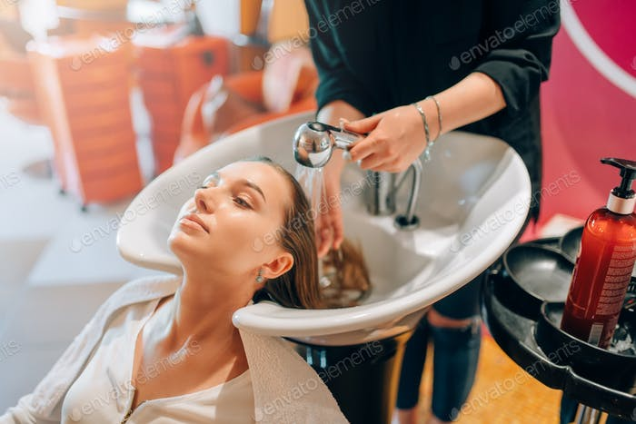 Hairdresser washes customer hair in basin