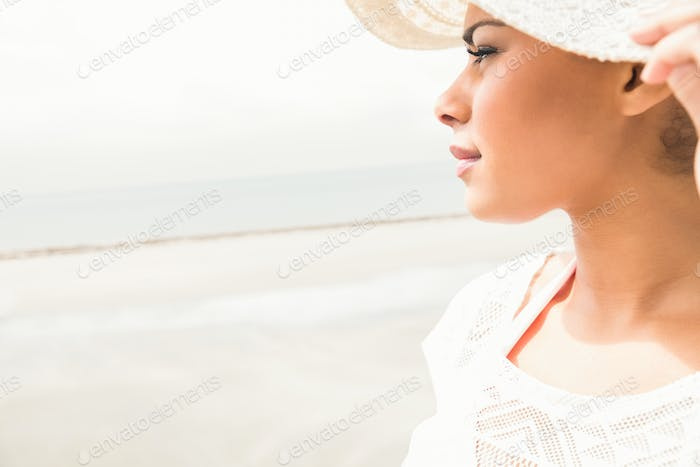 Stylish girl looking to the sea at the beach